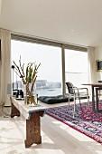 Zweige in Glasvase auf rustikaler Holzbank, gegenüber Stuhl aus Metall am Tisch, im Hintergrund raumhohes Fenster mit Aussicht auf Hafeneinfahrt