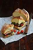 A sandwich with pesto, tomato confit and grilled vegetables