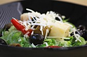 A mixed leaf salad with olives, peppers and cheese