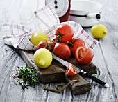 Fresh tomatoes, lemons and herbs on a chopping board in front of a pair of kitchen scales