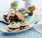 Biscuit sandwiches with cream, blueberries and icing sugar