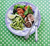 Pork medallions with penne pasta, pesto and a vegetables salad