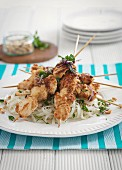 Chicken skewers on rice noodles