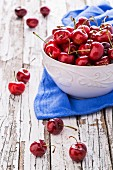 A bowl of fresh cherries on a blue cloth on a weathered wooden table