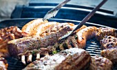 Meat, sausage and a rack of lamb on a barbecue
