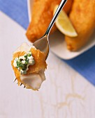 Battered fish with remoulade on a fork