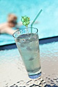 A lime drink with ice cubes by a pool