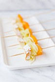 Skewers with rolled courgette ribbons, peaches and cheese on a serving platter
