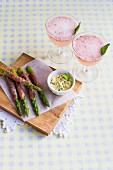 Asparagus wrapped in ham with basil mayonnaise served with strawberry cocktails