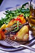 Eine Portion Gemüsetarte mit Kartoffeln und Rucola