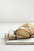 A loaf of sour dough bread on a chopping board with a tea towel