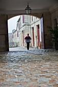 Mann trägt Gläser zum Verkostungssaal im Chateau Lafite-Rothschild (Bordeaux, Frankreich)