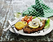 Breaded fish with capers, fried potatoes and tomato salad