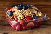 Müsli mit Erdbeeren und Heidelbeeren in Plastikschüssel