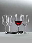 A glass of red wine and three empty wine glasses against a grey background