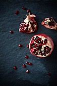 A pomegranate on a black slate platter