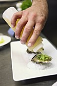 Oysters being drizzled with lemon juice