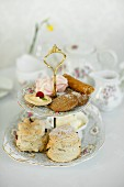 Scones and petit fours on a cake stand for afternoon tea