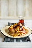 A stack of pancakes on a plate with grilled bacon and apple with maple syrup in the background