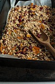 Homemade muesli in a baking tray with a wooden scoop