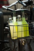 Homemade cucumber and lemonade in bottles in a bike basket