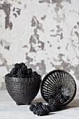 Two black baskets of fresh blackberries