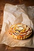 An apple tartlet on a piece of baking paper
