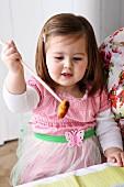 Kleines Mädchen isst mit Stäbchen