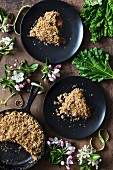 Rhubarb pie on a wooden surface with spring flowers and rhubarb leaves