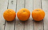 Three mandarins on a wooden surface