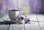 A cup of coffee and pansies