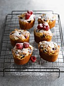 Friands with raspberries, lemons and flaked almonds on a wire rack