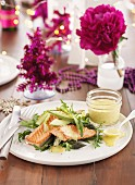 Fried salmon on a vegetable salad with avocado, asparagus and rocket
