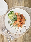 Salmon skewers on a rice noodle salad
