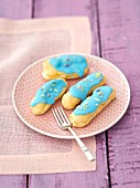 Eclairs with blue icing and dried pansy petals