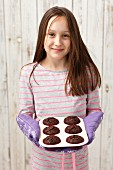 A girl holding freshly baked chocolate cupcakes