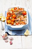 Baked salmon trout with potatoes, lemons and tomatoes