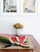 Sliced watermelon on chopping board and jug of flowers on table below framed drawings