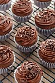 Schokoladencupcakes mit Buttercreme und Schokoraspeln auf Abkühlgitter