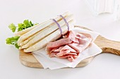 A bunch of white asparagus and ham on a chopping board