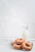 Sugar-glazed doughnuts with a bottle of milk