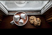 Cocoa with marshmallows and chocolate chip cookies in front of an old window