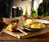 Potatoes being peeled with a knife with the peeled ones on a plate on a wooden board in a kitchen