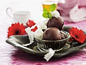 Chocolate soufflé balls with whipped cream and lemon balm