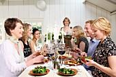 Freunde beim Mittagessen mit Nudelgericht, Gemüse und Rotwein