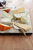 Verschiedene Käsesorten auf Holzbrett mit Käsemesser