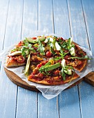 Tomato and avocado pizza topped with rocket