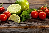 Cherry tomatoes, mint and limes on a wooden surface