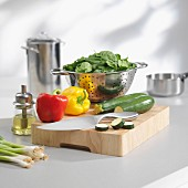 Spinach in a colander and vegetables on a chopping board