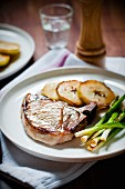 Pan fried pork chop with caramelised apple slices and fried spring onions